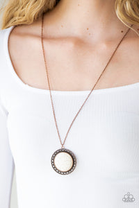 A refreshing white stone is pressed into the center of a shimmery copper frame radiating with sunburst details. The earthy frame swings from the bottom of a lengthened copper chain for a seasonal finish. Features an adjustable clasp closure.