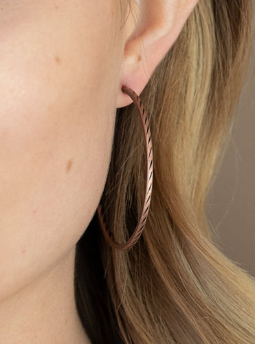 "Etched in a subtle slanted texture, a dainty copper hoop delicately curves around the ear in a rustic finish. Earring attaches to a standard post fitting. Hoop measures approximately 2"" in diameter.  Sold as one pair of hoop earrings.  Always nickel and lead free."