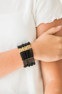 Joined together with metallic fittings, black seed beads are threaded along stretchy elastic bands. Sections of gold beads are sprinkled along the edgy layers, adding hints of shimmer to the seasonal palette.  Sold as one individual bracelet.  Always nickel and lead free.