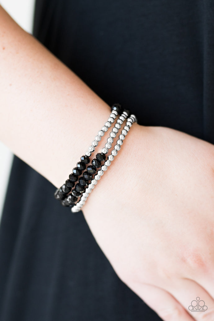 Brushed in an iridescent finish, faceted black beads and glistening silver beads are threaded along elastic stretchy bands, creating colorful layers across the wrist.  Sold as one set of three bracelets.  Always nickel and lead free.