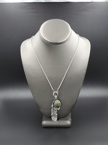 A round green stone and lifelike silver feather charm swing from the bottom of a lengthened silver chain, creating a whimsical pendant. Features an adjustable clasp closure.  Sold as one individual necklace. Includes one pair of matching earrings.  Always nickel and lead free.  Fashion Fix Exclusive November 2020