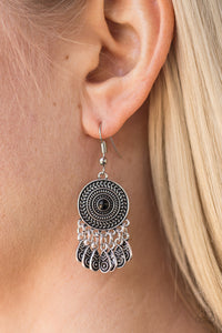 Radiating with a sunburst pattern, a glistening silver frame is dotted with a black bead. Brushed in an antiqued finish, ornate silver teardrops swing from the bottom of the tribal inspired frame, creating a whimsical lure. Earring attaches to a standard fishhook fitting.  Sold as one pair of earrings.  Always nickel and lead free.