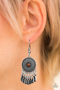 Radiating with a sunburst pattern, a glistening silver frame is dotted with a brown bead. Brushed in an antiqued finish, ornate silver teardrops swing from the bottom of the tribal inspired frame, creating a whimsical lure. Earring attaches to a standard fishhook fitting.  Sold as one pair of earrings.  Always nickel and lead free.