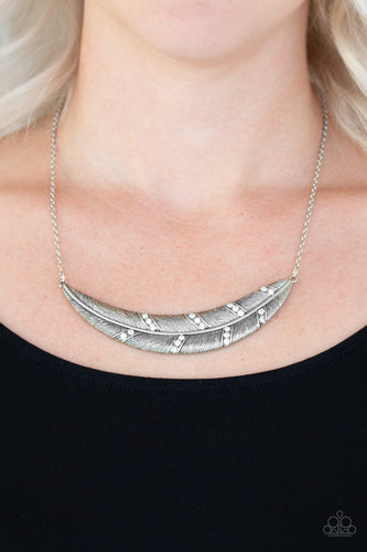 Dotted in sections of glittery white rhinestones, a lifelike silver feather pendant is suspended horizontally below the collar for a seasonal look. Features an adjustable clasp closure.  Sold as one individual necklace. Includes one pair of matching earrings.  Always nickel and lead free.