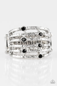 Delicately hammered in shimmer, dainty silver bars stack across the finger, coalescing into an airy band.