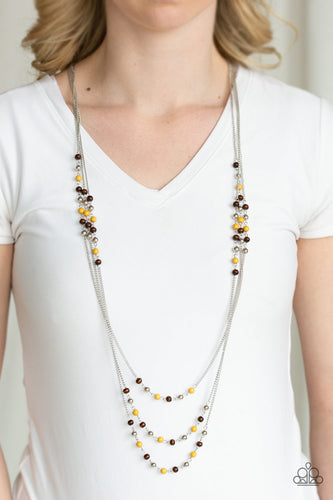 Dainty silver, yellow, and wooden beads trickle along three shimmery silver chains, creating colorful layers across the chest. Features an adjustable clasp closure.  Sold as one individual necklace. Includes one pair of matching earrings. Always nickel and lead free.