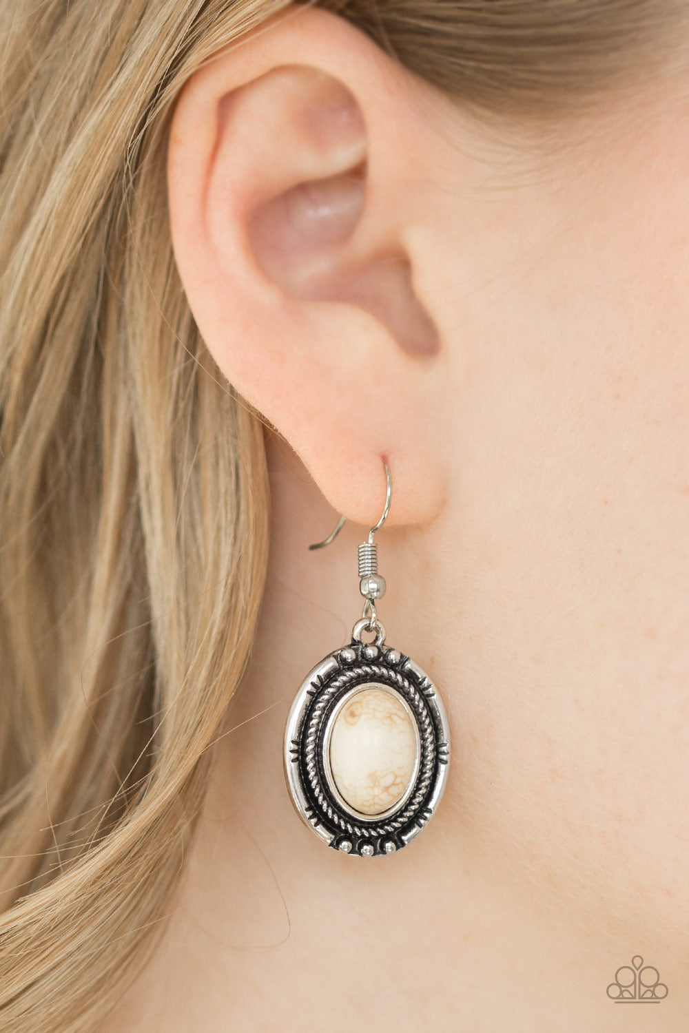 An earthy white stone is pressed into the center of a textured silver frame, creating a seasonal lure. Earring attaches to a standard fishhook fitting.  Sold as one pair of earrings.  Always nickel and lead free.