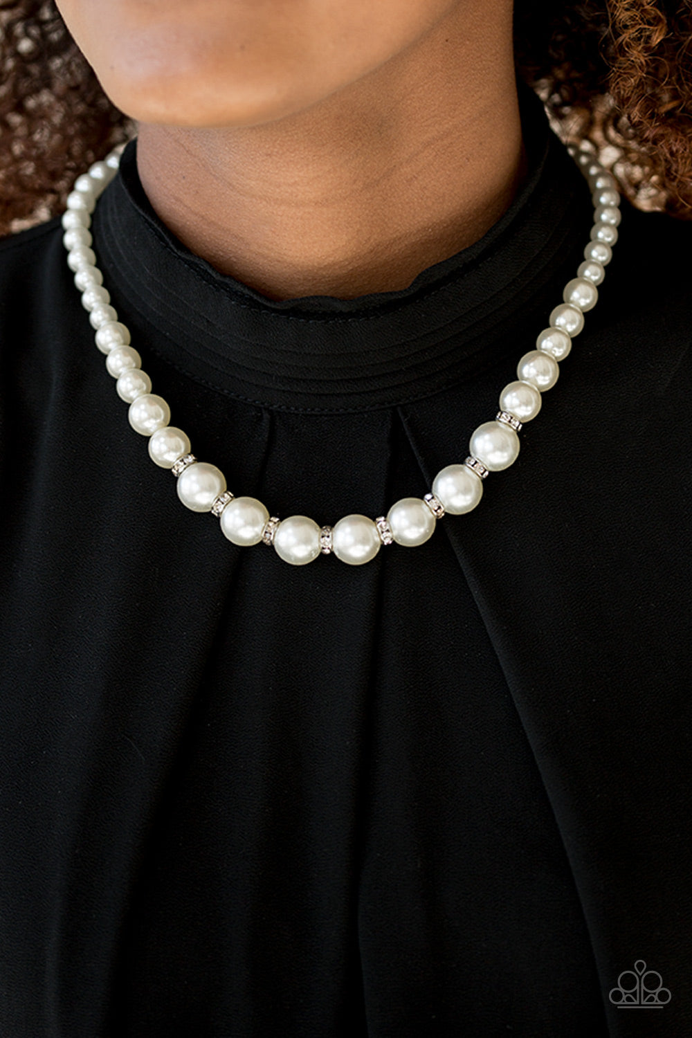 Gradually increasing in size near the bottom, classic white pearls drape below the collar. Rhinestone encrusted rings are sprinkled between the dramatic pearls, adding sparkling accents to the timeless pearl palette. Features an adjustable clasp closure.  Sold as one individual necklace. Includes one pair of matching earrings.  Always nickel and lead free.