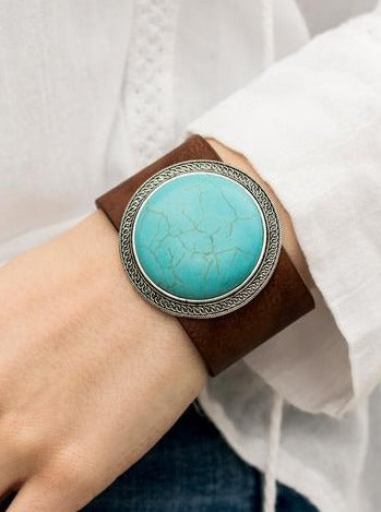 A dramatically over-sized turquoise stone is nestled inside a frame of radiating silver texture and studded in place at the center of a rustic brown leather band for a seasonal look. Features an adjustable snap closure.  Sold as one individual bracelet.