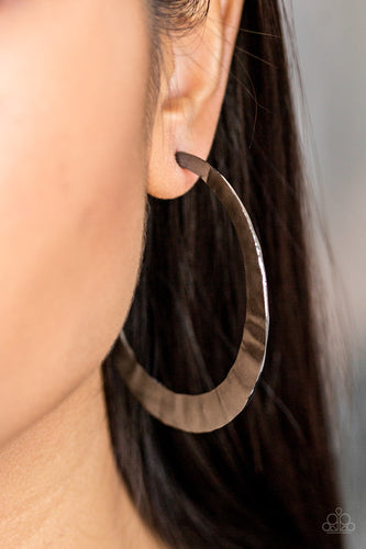 Brushed in a high-sheen finish, a delicately hammered silver hoop curls around the ear for a fierce look. Earring attaches to a standard post fitting. Hoop measures 2 1/2