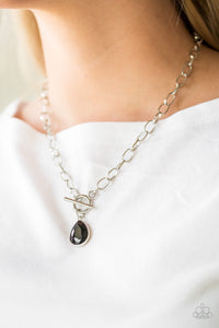 A faceted black teardrop gem swings from the bottom of a shimmery silver chain, creating a classic pendant below the collar. Features a toggle closure.  Sold as one individual necklace. Includes one pair of matching earrings.  Always nickel and lead free.