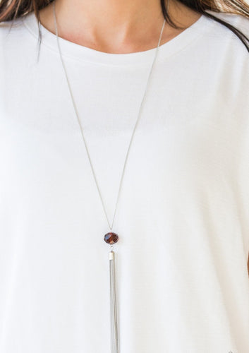 A glittery brown crystal-like bead swings from the bottom of a lengthened silver chain, giving way to a shimmering silver tassel for a glamorous finish. Features an adjustable clasp closure.  Sold as one individual necklace. Includes one pair of matching earrings.  Always nickel and lead free.