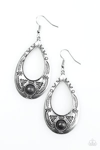 Stamped in tribal inspired patterns, a glistening silver teardrop swings from the ear