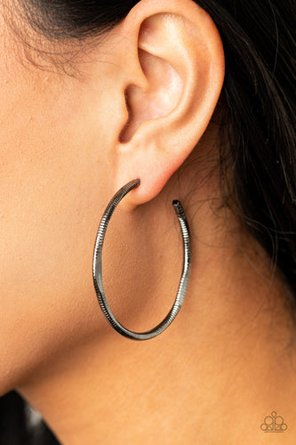 Featuring flattened sections, a textured gunmetal hoop boldly curls around the ear for an edgy flair. Earring attaches to a standard post fitting. Hoop measures approximately 1 3/4