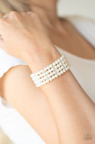 Held together by glittery white rhinestone encrusted silver fittings, row after row of white pearls are threaded along stretchy bands around the wrist for a timelessly stacked look.  Sold as one individual bracelet.  Always nickel and lead free.