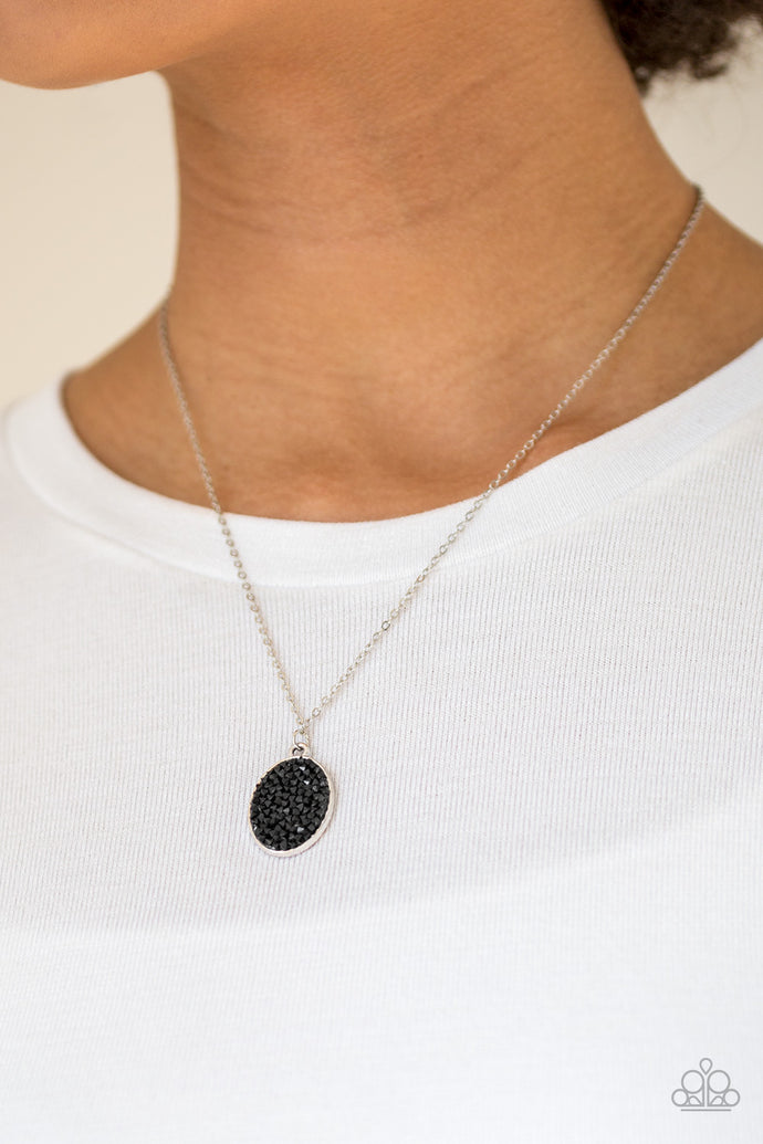 Glittery black rhinestones are sprinkled along an oval silver frame, creating a stellar pendant below the collar. Features an adjustable clasp closure.  Sold as one individual necklace. Includes one pair of matching earrings.  Always nickel and lead free.