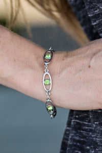 Sparkling green rhinestones adorn the center of glistening silver frames. The oval frames link around the wrist, creating a colorfully, refined palette. Features an adjustable clasp closure.  Sold as one individual bracelet.  Always nickel and lead free.