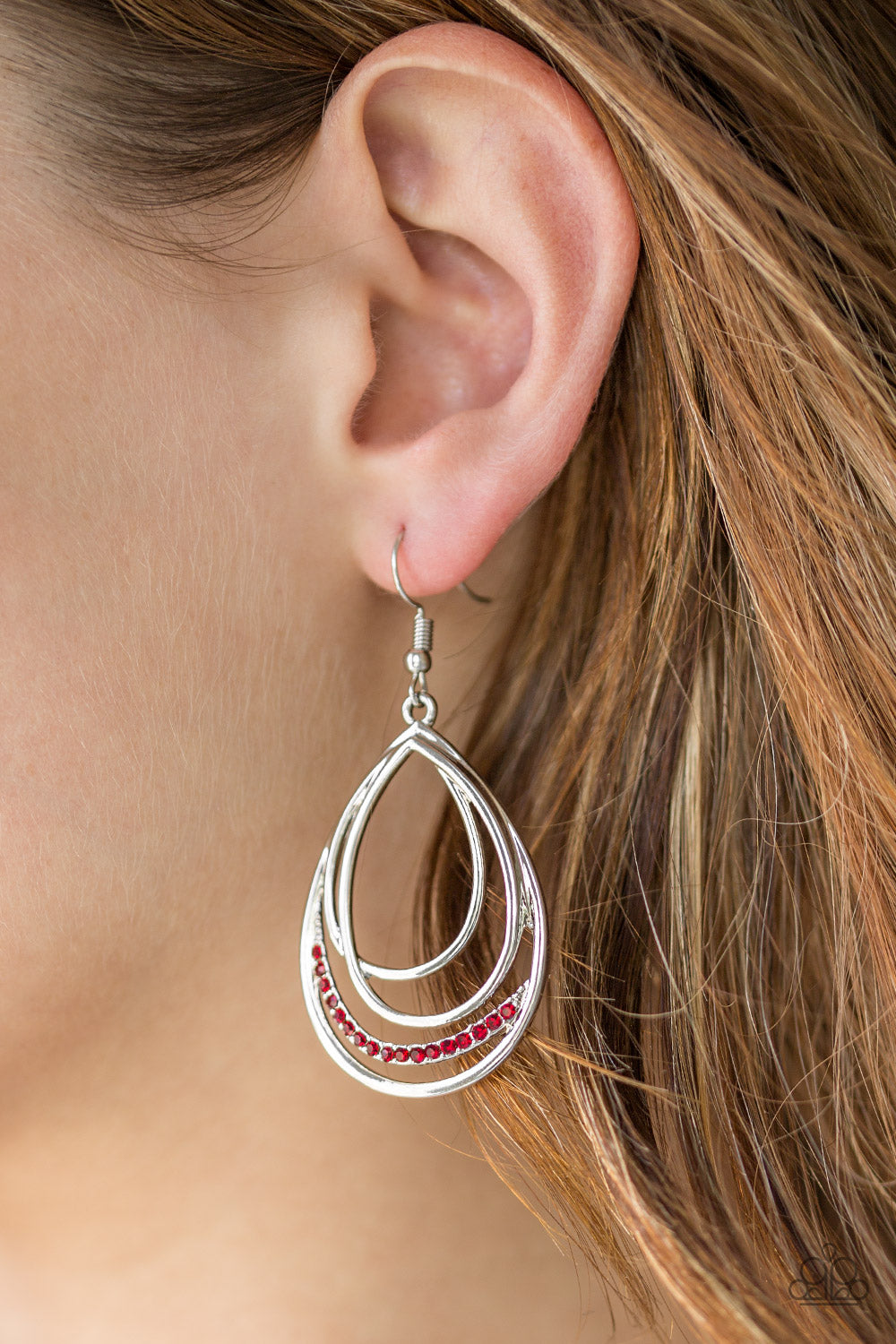 Shiny silver frames layer into an asymmetrical teardrop. A ribbon of glittery red rhinestones wraps around the bottom for a refined finish. Earring attaches to a standard fishhook fitting.  Sold as one pair of earrings.  Always nickel and lead free.