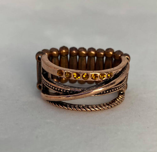Glittery topaz rhinestones dot two twisting copper bars, creating a glistening band. Features a stretchy band for flexible fit.  Sold as one individual ring.  Always nickel and lead free.  Fashion Fix Exclusive January 2021