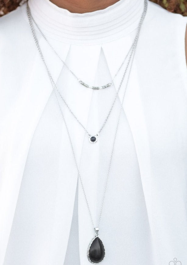 A textured silver bar is suspended horizontally from the uppermost chain above two stone pendants. A dainty black stone hangs from the center most layer as a black stone teardrop swings from the lowermost chain for a bold artisanal finish. Features an adjustable clasp closure.  Sold as one individual necklace. Includes one pair of matching earrings.  Always nickel and lead free.