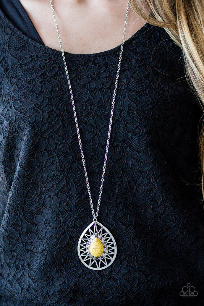 A sunny yellow stone is pressed into the center of a large silver teardrop radiating with shimmery sunburst patterns. The tribal inspired pendant swings from the bottom of a lengthened silver chain for a dramatic look. Features an adjustable clasp closure.  Sold as one individual necklace. Includes one pair of matching earrings.  Always nickel and lead free.