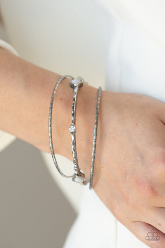 Infused with a pair of dainty textured bangles, a hammered silver bangle is encrusted in sections of glassy white rhinestones and square Paloma beads for a seasonal blend.  Sold as one set of three bracelets. Always nickel and lead free.