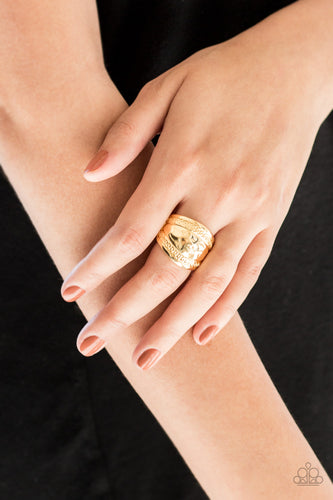 Ribbons of circular texture are embossed along the borders of a hammered gold band for an edgy look. Features a stretchy band for a flexible fit.  Sold as one individual ring.   Always nickel and lead free.