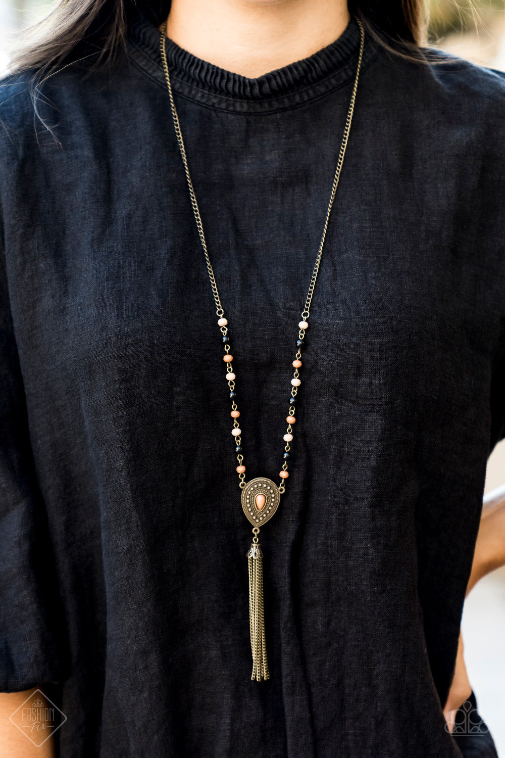 Polished black beads and faceted Almond Buff and Meerkat beads trickle along a brass chain, giving way to an antiqued teardrop pendant. Infused with studded detail and a matching Meerkat beaded center, the ornate pendant is decorated in a brass chain tassel for a wanderlust finish. Features an adjustable clasp closure.  Sold as one individual necklace. Includes one pair of matching earrings.   Sunset Sightings Fashion Fix December 2018  Always nickel and lead free.