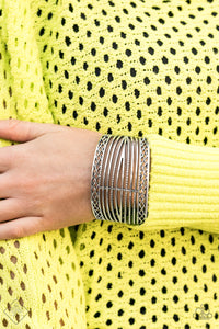 Bordered in crisscrossed details, hammering and smooth silver bars wrap back and forth across the wrist, coalescing into a thick silver cuff.