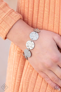 Gradually increasing in size, delicately hammered antiqued silver discs link around the wrist for a rustic flair. Features an adjustable clasp closure.  Ring:  Delicately hammered in shimmery details, glistening silver bands wrap
