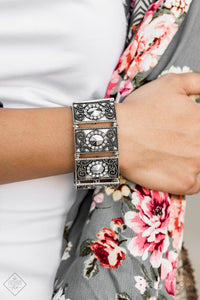 Featuring faceted silver beaded and white rhinestone encrusted centers, rectangular filigree filled silver frames are threaded along a stretchy band around the wrist for a vintage inspired look.