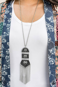 Silver beads encircled by rhinestones are nestled inside a row of three vintage frames that cascade down the chest at the bottom of an elongated silver chain. Glistening silver chains stream from the bottom of the stacked pendant, creating a gorgeously tapered tassel. Features an adjustable clasp closure.