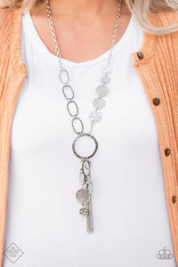 One row of hammered silver discs and one row of hammered oval links give way to an oversized hammered silver hoop. A collection of silver discs, hammered links, abstract silver pieces, and a shimmery silver chain tassel dangle from the hoop, creating a one-of-a-kind pendant. Features an adjustable clasp closure.