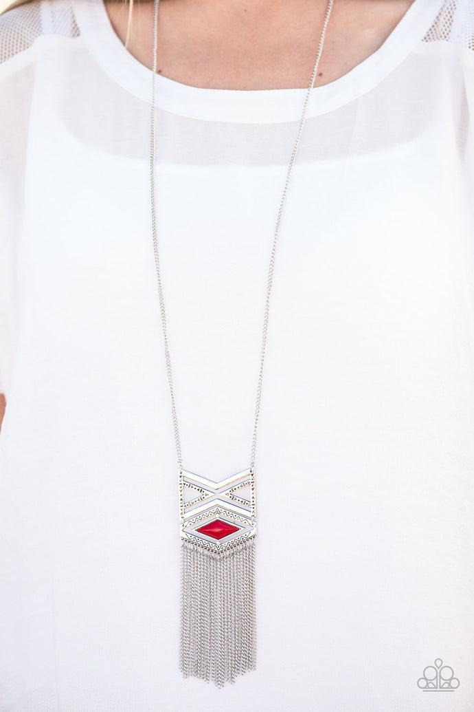 Stamped in triangular patterns, a dramatic tribal inspired pendant swings from the bottom of a shimmery silver chain in an indigenous fashion. Shimmery silver chains stream from the bottom of the pendant as a fiery red bead is pressed into the frame for a colorful finish. Features an adjustable clasp closure.  Sold as one individual necklace. Includes one pair of matching earrings.  Always nickel and lead free.