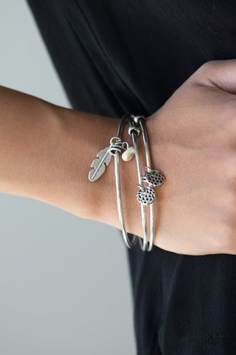 Hammered silver discs, a silver feather, and a white pebble slide along three antiqued silver bangles for a seasonal look.  Sold as one set of three bracelets.  Always nickel and lead free.