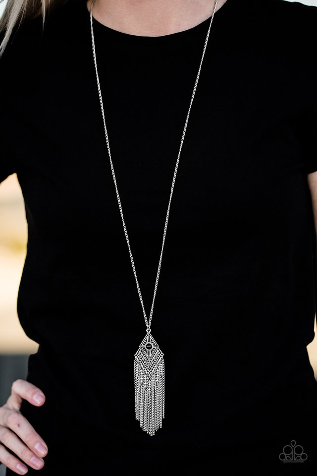 A black bead is pressed into the center of a kite-shaped pendant. Embossed in tactile textures, the shimmery pendant gives way to a whimsical chain tassel featuring dainty beaded accents. Features an adjustable clasp closure.  Sold as one individual necklace. Includes one pair of matching earrings.  Always nickel and lead free.