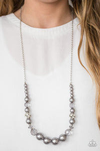 Pearly silver and glittery white crystal-like beads are threaded along the bottom of an elongated silver chain. The beads decrease in size as they climb the chain, while sparkling accents are sprinkled between them for a glamorous finish. Features an adjustable clasp closure.  Sold as one individual necklace. Includes one pair of matching earrings.  Always nickel and lead free.
