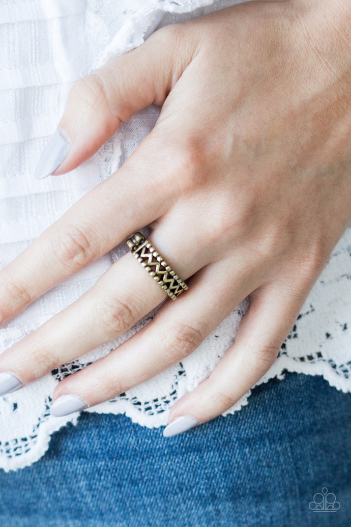 A shimmery brass bar zigzags down the center of a studded band for a tribal inspired look. Features a dainty stretchy band for a flexible fit.  Sold as one individual ring.  Always nickel and lead free.