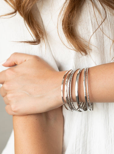 Featuring an array of smooth, hammered, and metallic rope-like textures, a mismatched collection of shiny silver bangles stacks across the wrist for a classic look.  Sold as one set of seven bracelets.  Always nickel and lead free.