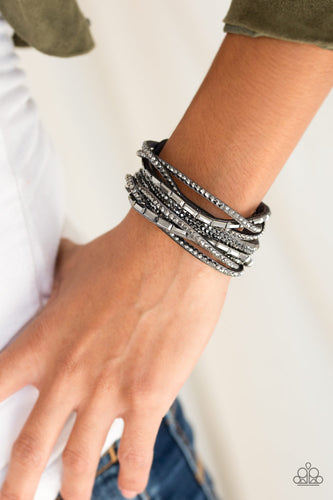 Featuring edgy emerald and classic style cuts, glittery hematite rhinestones are encrusted along crisscrossing strands of gray suede for a fierce one-of-a-kind look. Features an adjustable snap closure.  Sold as one individual bracelet.  Always nickel and lead free.