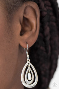 Etched in serrated shimmer, two silver teardrops drip from the ear in a refined fashion. A pearly white bead swings from the center of the airy lure, adding a colorful finish to the elegant palette. Earring attaches to a standard fishhook fitting.  Sold as one pair of earrings.  Always nickel and lead free.