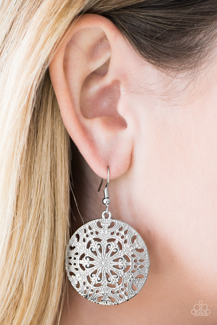 Brushed in a distressed gray finish, an ornate circular frame swings from the ear in a whimsical fashion. Earring attaches to a standard fishhook fitting.  Sold as one pair of earrings.  Always nickel and lead free.