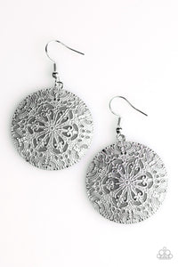 Brushed in a distressed gray finish, an ornate circular frame swings from the ear.