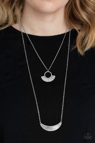 Radiating with linear patterns, a flared silver frame swings above a silver half-moon frame, creating tribal inspired layers below the collar. Features an adjustable clasp closure.  Sold as one individual necklace. Includes one pair of matching earrings.  Always nickel and lead free.