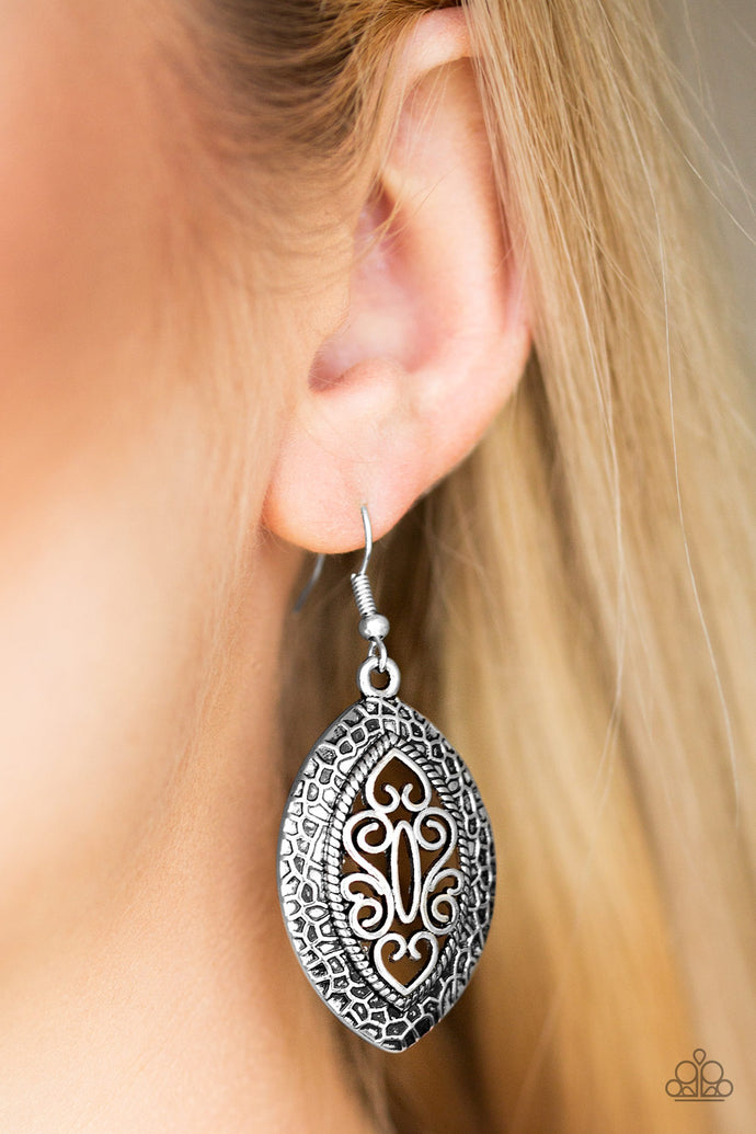 Featuring filigree filled details, a shimmery silver frame swings from the ear for a tribal inspired look. Earring attaches to a standard fishhook fitting.  Sold as one pair of earrings.  Always nickel and lead free.