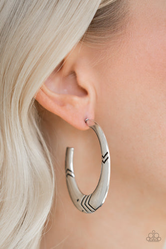 V-shaped geometric patterns are stamped along a flat silver hoop for a bold, tribal inspired look. Earring attaches to a standard post fitting. Hoop measures 1 1/4