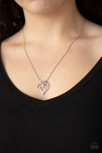 A pink rhinestone encrusted heart intertwines with two plain silver heart frames, stacking into a romantic pendant at the bottom of a sleek silver chain. Features an adjustable clasp closure.  Sold as one individual necklace. Includes one pair of matching earrings. Always nickel and lead free.