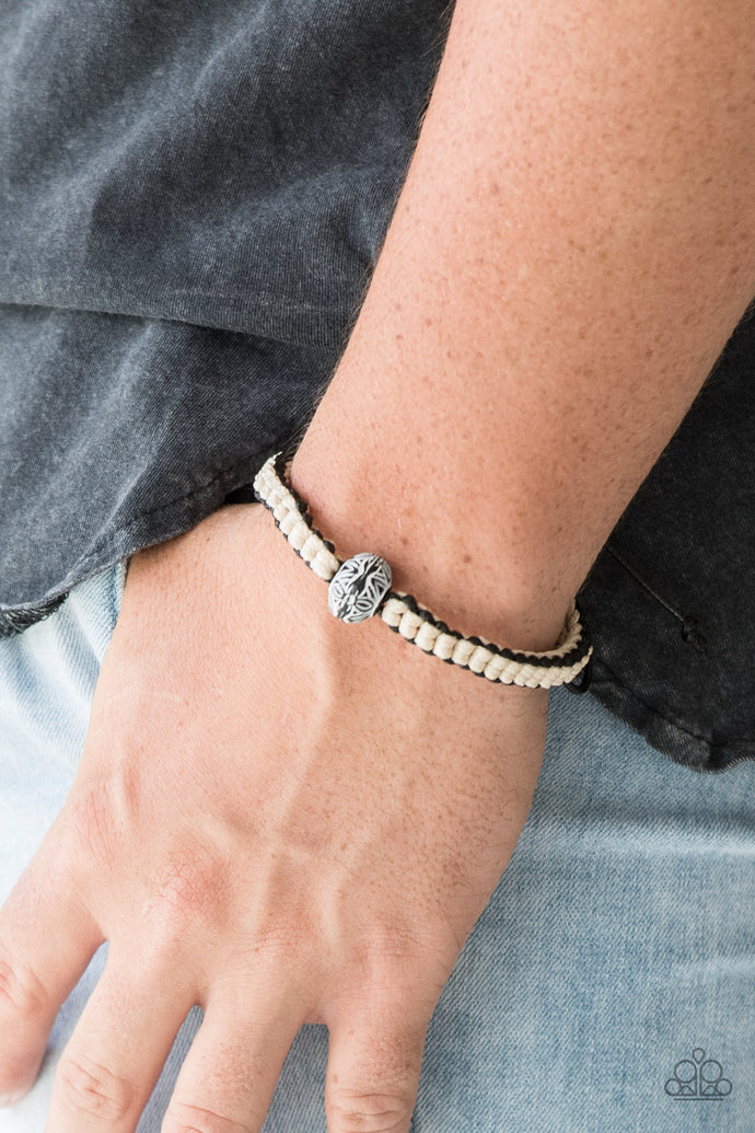 Black and off-white cording knot around the wrist, creating a colorful braid. Featuring floral like detail, a black bead adorns the center for a seasonal finish. Features an adjustable sliding knot closure.  Sold as one individual bracelet.   Always nickel and lead free.
