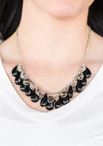 Polished black teardrops drip from the bottom of a shimmery silver chain, creating a colorful fringe below the collar. Featuring a delicately hammered surface, dainty silver teardrops are sprinkled along the chain for a splash of eye-catching shimmer. Features an adjustable clasp closure.  Sold as one individual necklace. Includes one pair of matching earrings.  Always nickel and lead free.