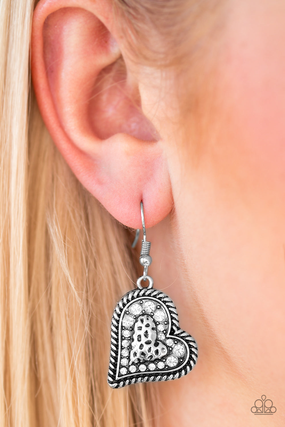 Encrusted in glittery white rhinestones, the center of a heart shaped frame is embossed in a textured heart for a flirty finish. Earring attaches to a standard fishhook fitting.  Sold as one pair of earrings.  Always nickel and lead free.